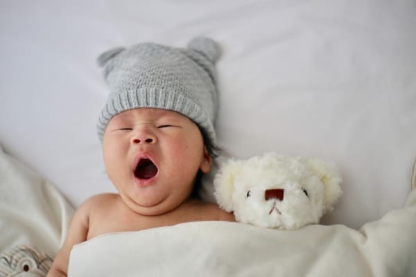 A newborn yawns while next to its teddy bear.